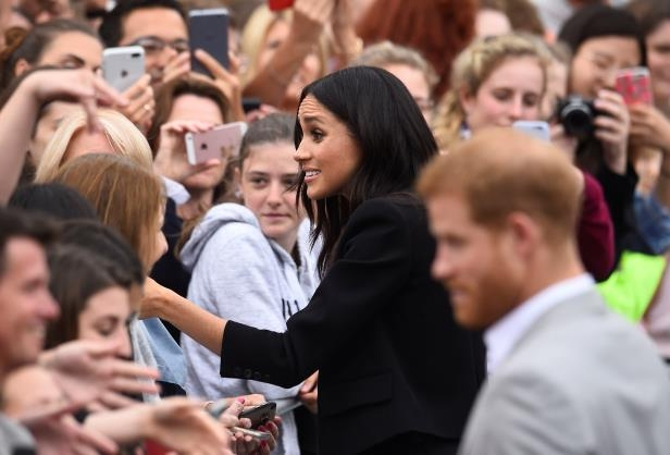 Slide 4 of 86: Britain's Prince Harry and Meghan, the Duchess of Sussex, shake hands with members of the crowd during a walkabout in Parliament Square in Trinity College, Dublin, Ireland, July 11, 2018. REUTERS/Clodagh Kilcoyne