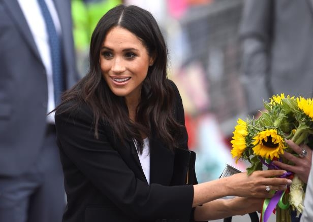 Slide 7 of 86: Britain's Meghan, the Duchess of Sussex, accepts some flowers during a visit to Parliament Square in Trinity College, Dublin, Ireland, July 11, 2018. REUTERS/Cathal McNaughton