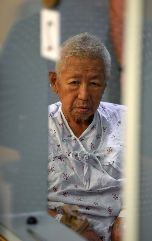 Thomas Kim sits in a hospital gown in a wheelchair as his arraignment is postponed in Superior Court in Long Beach, Calif., on Monday, July 9, 2018. Kim, the 77-year-old man suspected of setting off an explosion in his Long Beach apartment building on June 25, then opening fire on two firefighters, killing Fire Capt. David Rosa, had his arraignment postponed until August 15. (Scott Varley/The Orange County Register via AP, Pool)