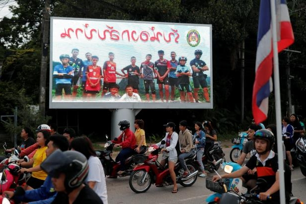"a group of people riding on the back of a motorcycle: A billboard reading ""Welcome home, boys"" in Chiang Rai Province on Monday."