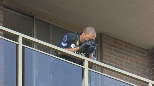 a man standing in front of a window: A Hamilton police officer takes photos from a balcony at Villa Marie II, an apartment tower at 50 Young St., on Wednesday. Reports say, a six-year-old boy died after falling from a sixth-floor balcony in the afternoon.