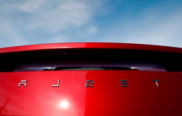 FILE - In this April 15, 2018, file photo, the sun shines off the rear deck of a roadster on a Tesla dealer's lot in the south Denver suburb of Littleton, Colo. Electric car producer Tesla says it will build its first factory outside the United States in Shanghai. Tesla says an agreement signed Tuesday, July 10, with a Shanghai city government agency calls for construction to start in the near future. (AP Photo/David Zalubowski, File)
