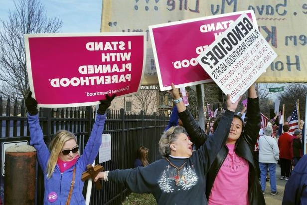 FILE - In this Feb. 11, 2017, file photo, a Planned Parenthood supporter and opponent try to block each other's signs during a protest and counter-protest of abortion in St. Louis. If a Supreme Court majority shaped by President Donald Trump overturns or weakens the right to abortion, the fight over its legalization could return to the states. (AP Photo/Jim Salter, File)