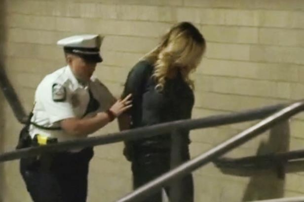 In this frame from video, porn actress Stormy Daniels is led into jail in Columbus, Ohio., after being taken into custody during a Wednesday evening, July 11, 2018, show. Daniels was arrested at a strip club and is accused of letting patrons touch her in violation of a state law, her attorney said early Thursday, July 12. (WBNS via AP)