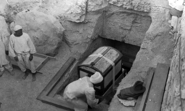 Slide 17 of 18: King Tut - Worldwide interest has been aroused in the discovery and now the removal of ancient treasures valued at $15,000,000 from the tomb of King Tutankhamen, who breigned #3500 years ago, at Luxor, Egypt. treasures are now being removed from the outer tomb under the direction of Howard Carter, American archaeologist, who with Lord Carnarvon, headed the expedition of discovery. Natives just emerging from outer tomb with a large white box, resembling modern trunk, containing valuable fabrics. A group of cartouches representing names of King and Queen was painted on the front of the box in gold upon a blue background. (Photo By: /NY Daily News via Getty Images) New York Daily News/NY Daily News via Getty Images/Getty Images