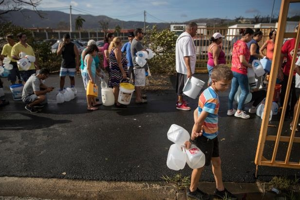 a group of people standing in front of a crowd: People waited in line for drinking water outside a police station in Juncos, P.R., four days after Hurricane Maria made landfall.