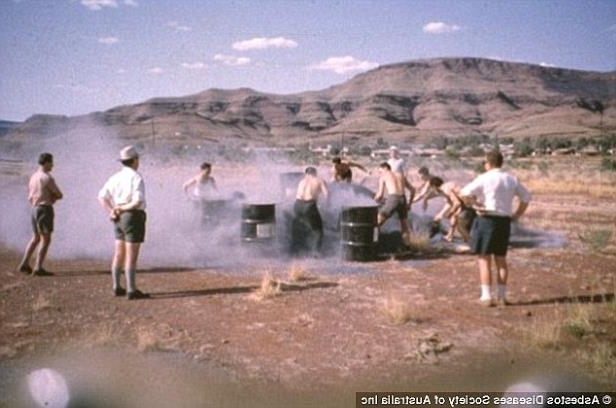 a group of people walking down a dirt road: Miners playing an asbestos shovelling competition in the West Australian town of Wittenoom in 1962. All of the men in the image but one have since died from exposure to the deadly mineral