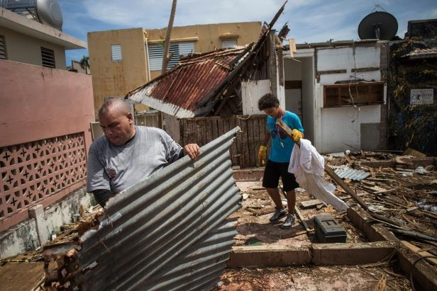 a man standing in front of a brick building: Moises Martinez, right, removed debris from his home in San Juan. The Federal Emergency Management Agency said in a draft report that it had not planned adequately for a disaster in Puerto Rico on the vast scale of Hurricane Maria.