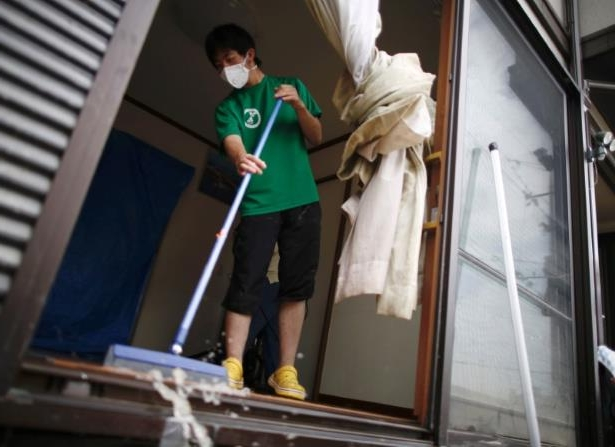 a person standing in front of a building: A local resident tries to clear mud and debris from his home at a flood affected area in Mabi town in Kurashiki