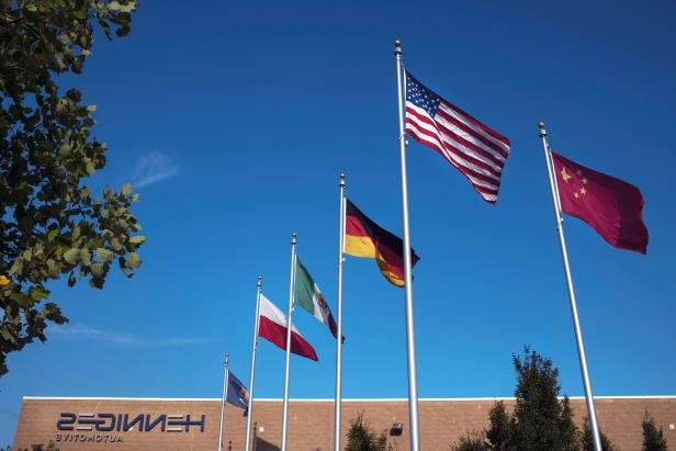 a sign in front of a flag: China's flag flies high above Henniges Automotive in Auburn Hills, Mich., reflecting the global nature of the state's auto industry.