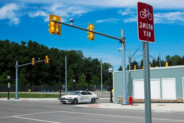 a traffic light on a city street: A Lincoln makes its way around MCity, a replica city track imitating real life traffic stops and turns, during a demo showcasing the car's driverless capabilities at the University of Michigan.