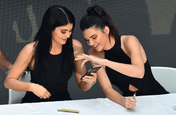 a woman sitting on a table: Kylie Jenner (right) and her sister Kendall.