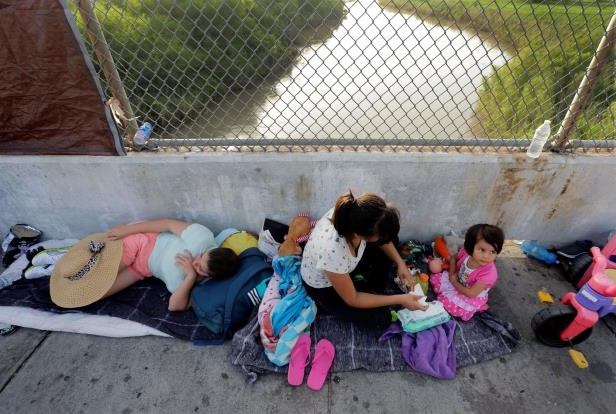 Immigrants from Cuba and Guatemala seeking asylum in the United States wait on the Matamoros International Bridge above the Rio Grande, Friday, June 29, 2018, in Matamoros, Mexico. (AP Photo/Eric Gay, File)