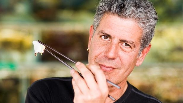 Anthony Bourdain talking on a cell phone