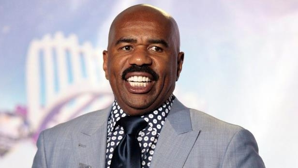 Steve Harvey wearing a suit and tie smiling at the camera: Steve Harvey is set to return as the 2018 Miss Universe host this December.