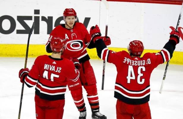a group of people skiing on the snow: The Carolina Hurricanes' Jeff Skinner (53) celebrates his game-winning goal with Jaccob Slavin (74) and Phillip Di Giuseppe (34) after he scored during the third period against the Arizona Coyotes at PNC Arena in Raleigh, N.C., on March 22, 2018.