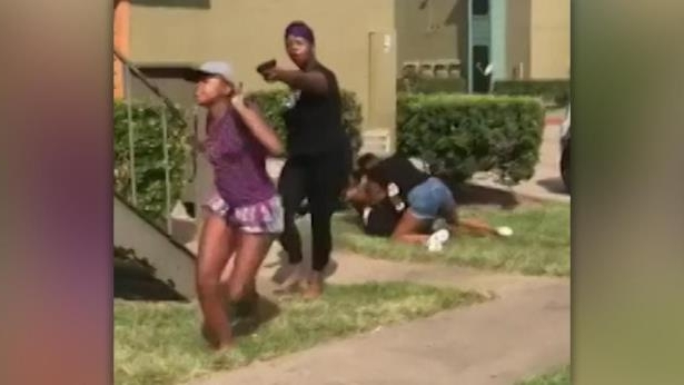 a person standing in front of a building: Raw video: Mother says she pulled a BB gun during daughter's fight with a teenage girl who arrived with a large group who had a knife.
