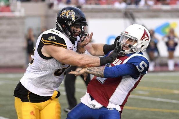 Montreal Alouettes quarterback Johnny Manziel (2) is hit by Hamilton Tiger-Cats defensive end Jason Neill (96) during the first half of a Canadian Football League game Friday, Aug. 3, 2018, in Montreal. (Paul Chiasson/The Canadian Press via AP)
