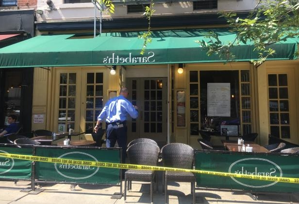 a green chair in front of a building: Police tape was wrapped around Sarabeth's restaurant on Manhattan's Upper West Side after a man died there on Sunday.