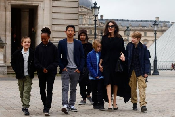 a group of people posing for the camera: Shiloh Jolie-Pitt, Angelina Jolie, Vivienne Jolie-Pitt, Pax Jolie-Pitt, Maddox Jolie-Pitt, Zahara Jolie-Pitt and Knox Jolie-Pitt visit the Louvre in Paris on Jan. 30, 2018.