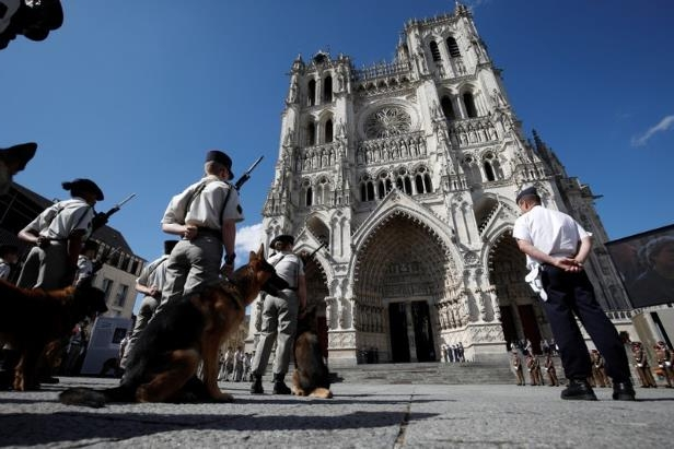 a group of people standing in front of a building: French soldiers and their dogs stand outside the cathedral after a religious ceremony to mark the 100th anniversary of the World War I (WW1) Battle of Amiens