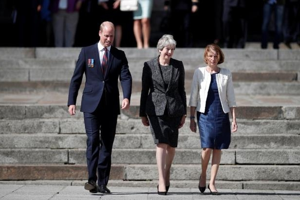 a man wearing a suit and tie walking on a sidewalk: Britain's Prince William, the Duke of Cambridge, Britain's Prime Minister Theresa May, and French Minister of the Armed Forces Florence Parly leave after a religious ceremony to mark the 100th anniversary of the World War I (WW1) Battle of Amiens