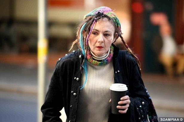 a person is walking down the street talking on a cell phone: Pictured is axe attack victim Sharon Hacker, who Evie Amati tried to kill at a Sydney convenience store