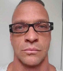 a man wearing glasses: Photo shows death-row inmate Scott Raymond Dozier.