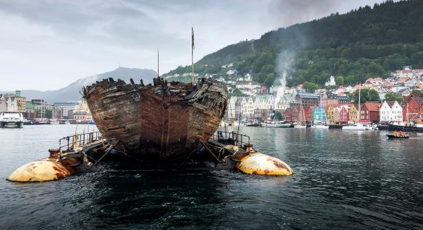 a small boat in a body of water: The wreck of the Maud is towed into the Norwegian port of Bergen.