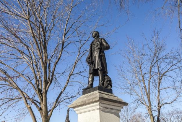 a tall clock tower sitting under a tree: A statue of Sir John A. Macdonald on Parliament Hill in Ottawa. Victoria B.C.'s removal of a statue of the first PM has reignited a national debate.
