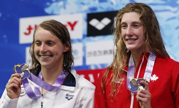 Canada's Taylor Ruck, left, reacts on the podium after winning the women's 200m freestyle final with third placed Katie Ledecky of the US at the Pan Pacific swimming championships in Tokyo, Japan, Thursday, Aug. 9, 2018. (AP Photo/Shuji Kajiyama)