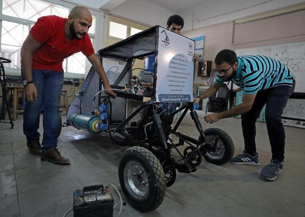 Mechanical engineering students from Helwan University check the air-powered vehicle that they have designed to promote clean energy and battle increasing gas prices, in Cairo