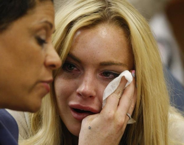 Slide 21 of 37: Lindsay Lohan (L) cries next to her lawyer Shawn Chapman Holley as she is sentanced to 90 days jail by Judge Marsha Revel during her hearing at the Beverly Hills Courthouse on July 6, 2010.  Troubled Hollywood starlet Lindsay Lohan broke down in tears after she was sentenced to 90 days in jail for violating her probation in two 2007 drunk driving cases. The actress, once a red-headed Disney films star and promising A-lister whose career since has spun off course, also was ordered to participate in a 90-day inpatient substance abuse program. After Beverly Hills Superior Court Judge Marsha Revel sentenced Lohan, 24, the actress and fashion muse wept in court.                  AFP PHOTO / POOL / David McNew (Photo credit should read DAVID MCNEW/AFP/Getty Images)