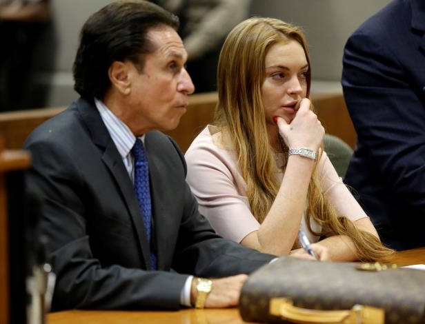 Slide 25 of 37: LOS ANGELES, CA - MARCH 18:  Actress Lindsay Lohan and attorney Mark Heller listen at a hearing in Los Angeles Superior Court on March 18, 2013 in Los Angeles, California. The hearing is to determine whether Lohan returns to jail or averts a trial on charges that she lied to police over a June, 2012 car crash that briefly sent her to the hospital.  Lohan has pleaded not guilty to three misdemeanor charges filed after the accident - reckless driving, lying to police and obstructing officers from performing their duties.  (Photo by Reed Saxon - Pool/WireImage)