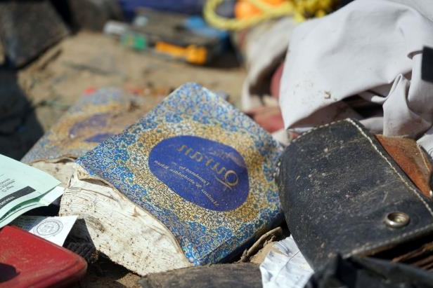 A battered Quran sits among other items strewn about a compound in Amalia, New Mexico, following a law enforcement raid that ended with the arrest of five adults on child-abuse charges and 11 children being rescued.