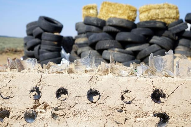 a close up of a desert: Broken glass embedded in the top of a mud wall built by adults living in a compound in Amalia, New Mexico, fronting a secondary wall made of dirt-filled tires.