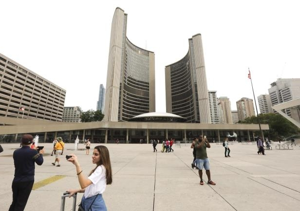 a group of people standing in front of a building: An anti-Islam rally planned for Saturday at Nathan Phillips Square has been postponed following backlash from city councillors, organizations and officials.
