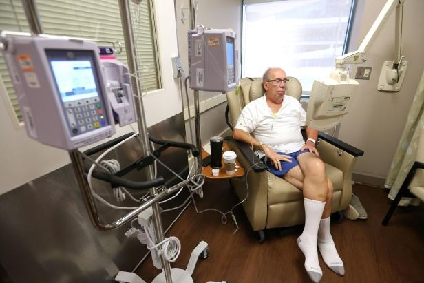 a man sitting on a table: Bob Rulli undergoes a transfusion of the experimental drug BXQ-350, which lasted about an hour, Tuesday, July 10, 2018, at the University of Cincinnati's Barrett Cancer Center in Cincinnati.