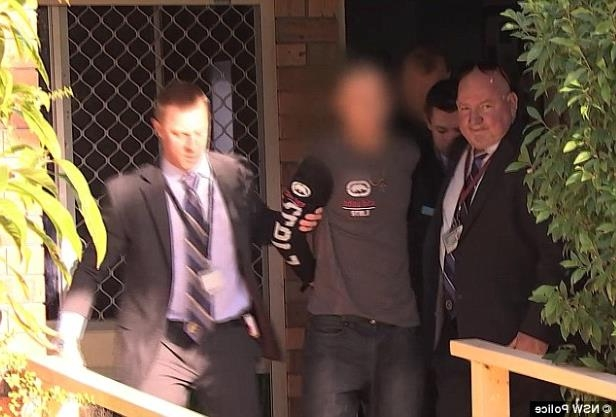 a person standing posing for the camera: Police arrested Whiteley (pictured centre) at a Tanilba Bay home on Thursday morning