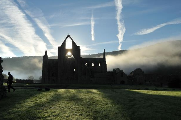 Autumn sun rises behind Tintern Abbey in the Wye Valley.