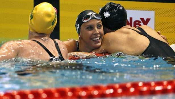 Christy Turlington in a swimming pool: Canada's Kylie Masse, centre, celebrates her victory in the women's 100m backstroke at the Pan Pacific Swimming Championships in Tokyo.