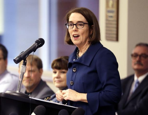 FILE - In this Feb. 2, 2018 file photo, Oregon Gov. Kate Brown speaks in Portland, Ore. The evangelist Franklin Graham recently asked thousands of people at an Oregon rally to pray for the state's Democratic governor, saying she should be a Christian. Yoga and meditation suit Brown just fine, she told reporters Thursday, Aug. 9, 2018, when asked if she follows a certain faith. (AP Photo/Don Ryan, File)
