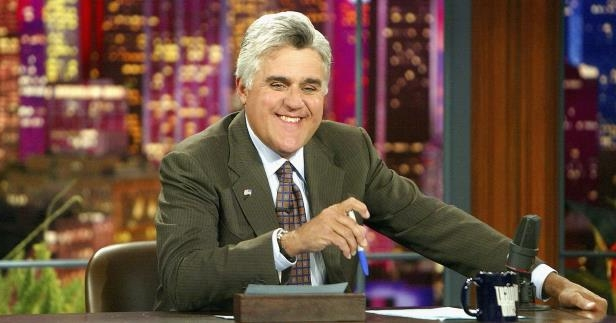 Jay Leno wearing a suit and tie sitting at a table