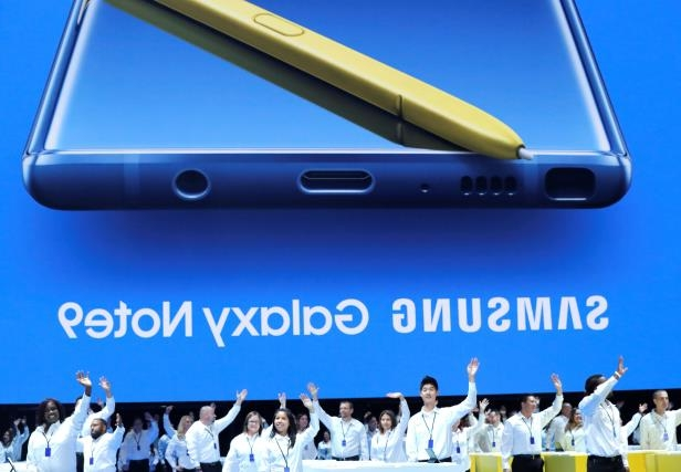 Samsung employees wave from stage beneath an image of the new Samsung Galaxy Note 9 during a product launch event in Brooklyn, New York, U.S., August 9, 2018. REUTERS/Lucas Jackson