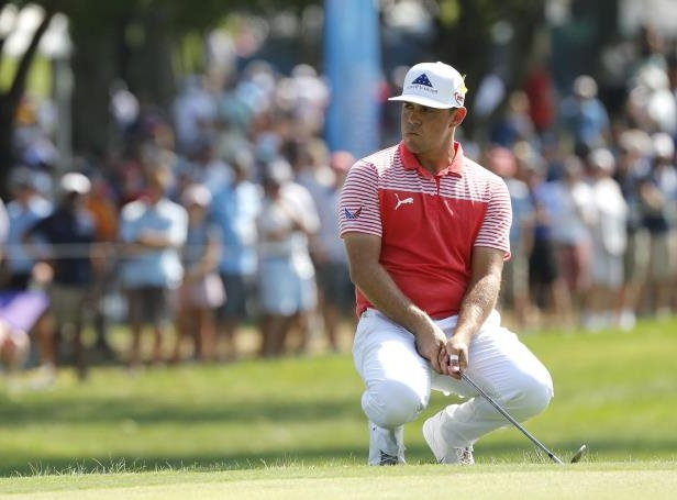 a person holding a baseball bat on a field: Gary Woodland missed this putt on the first green, but not much else during the second round of the PGA Championship at Bellerive n St. Louis.