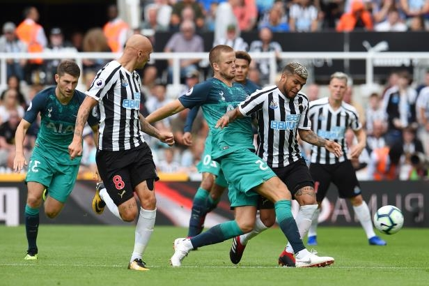 a group of young men playing a game of football: NEWCASTLE UPON TYNE, ENGLAND - AUGUST 11: Deandre Yedlin of Newcastle United is challenged by Eric Dier of Tottenham Hotspur during the Premier League match between Newcastle United and Tottenham Hotspur at St. James Park on August 11, 2018 in Newcastle upon Tyne, United Kingdom.