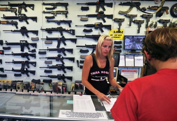 FILE--In this 2014 file photo, a gun store employee helps a customer in Colorado.