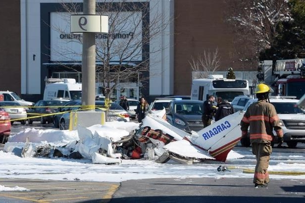 A firefighter and police officers look at the wreckage from a plane crash sits in a parking lot in Saint-Bruno, Que., on March 17, 2017. THE CANADIAN PRESS/Ryan Remiorz