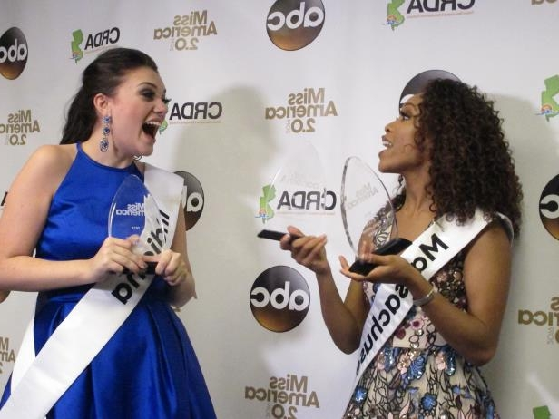 Miss Massachusetts Gabriela Taveras, left, and Miss Indiana Lydia Tremaine celebrate after winning preliminary competition awards in the Miss America pageant Friday Sept. 7, 2018 in Atlantic City, N.J. Taveras won the onstage interview and Tremaine won the talent portion. (AP Photo/Wayne Parry)