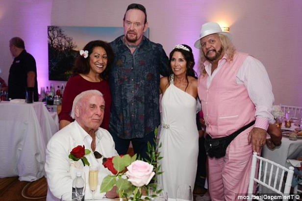 a group of people posing for the camera: Outside of the ring: Michael Hayes, The Undertaker and Ata Johnson posed with the happy couple during the reception